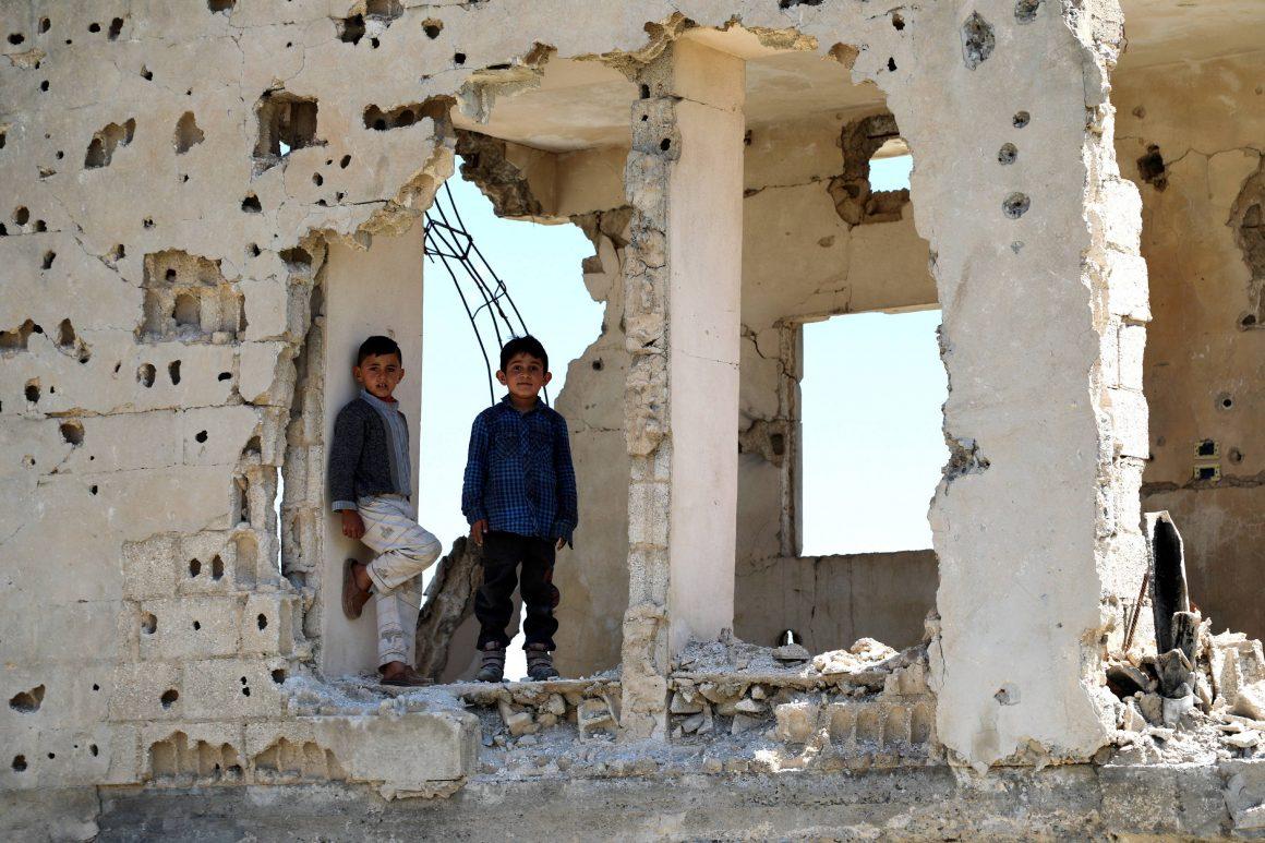SYRIAN KURDISH BOYS LOOK THROUGH A DESTROYED BUILDING IN KOBANÎ (ALSO CALLED AYN AL-ARAB), THE KURDISH REGION IN THE ALEPPO GOVERNORATE IN NORTHERN SYRIA, APRIL 26, 2019.© AHMED MARDNLI (PAP/EPA)